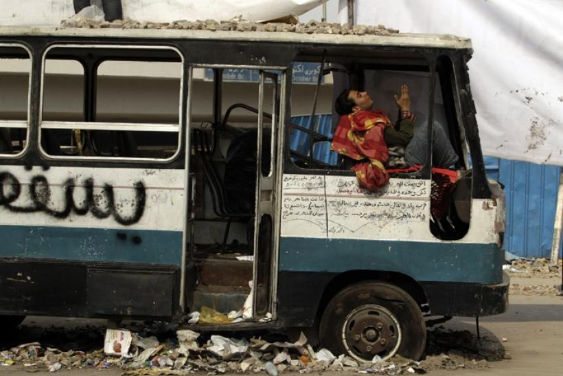 An opposition supporter prays while sitting in a damaged bus near Tahrir Square in Cairo