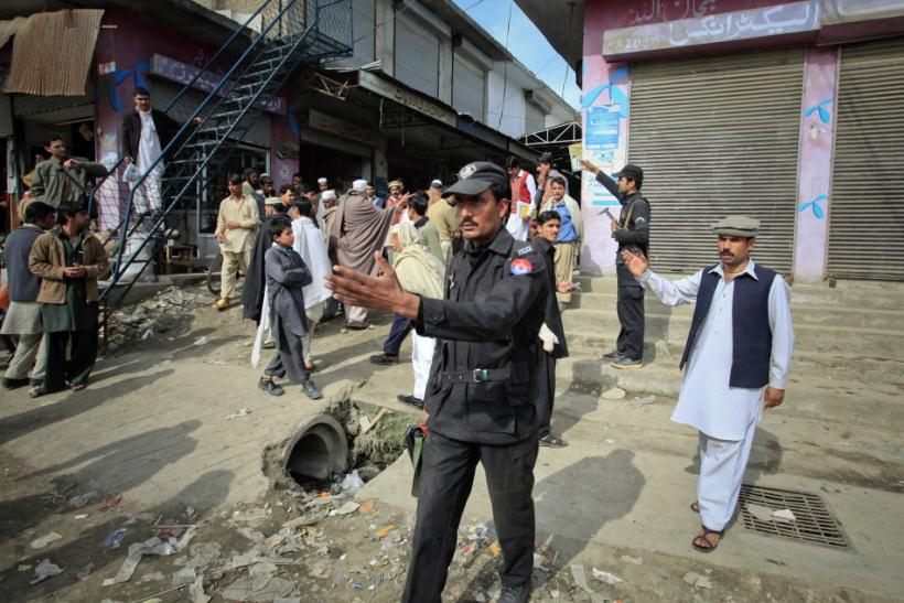 Policemen ask residents to disperse as they stand near the site of a suicide bomb attack at a paramilitary training centre in Mardan, northwest Pakistan February 10, 2011.