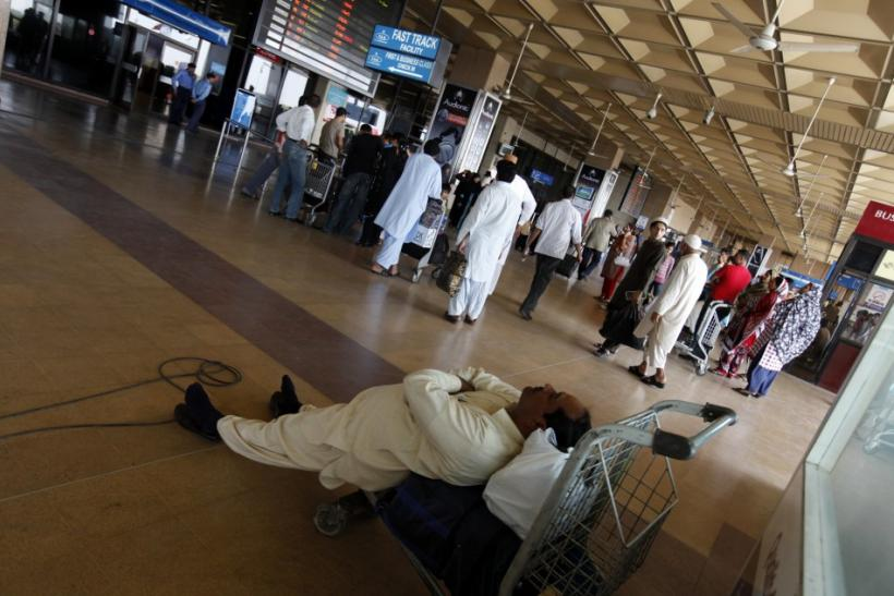 Passenger naps on his luggage while waiting to get on flight, which was cancelled due to strike by employees of Pakistan International Airlines, at Karachi's Jinnah International Airport