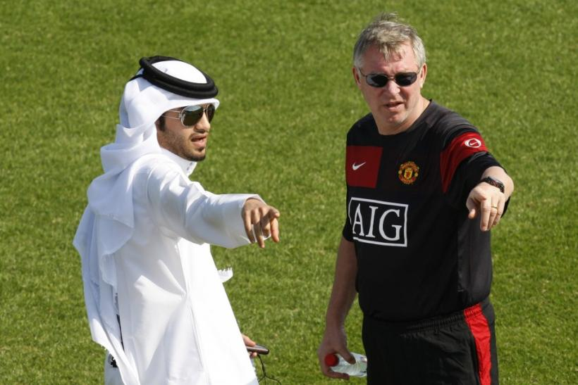 Manchester United's coach Alex Ferguson (R) talks to a facilities assistant during a training session at the Aspire Academy for Sports Excellence in Doha on Jan 2010.