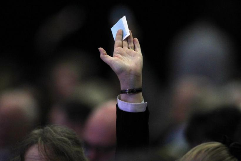 A man holds his ballot paper in the air for collection during the federation of small businesses conference in Aberdeen