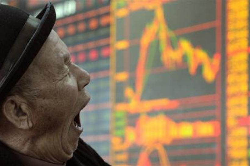 A man yawns in front of an electronic board showing stock information at a brokerage house in Taiyuan, Shanxi province