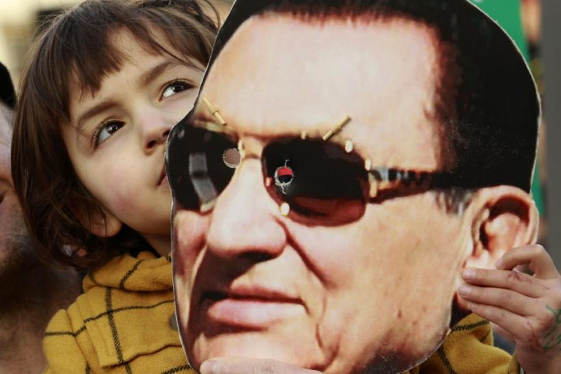 A child holds a mask of Egypt's former President Hosni Mubarak during a rally in Trafalgar Square in central London
