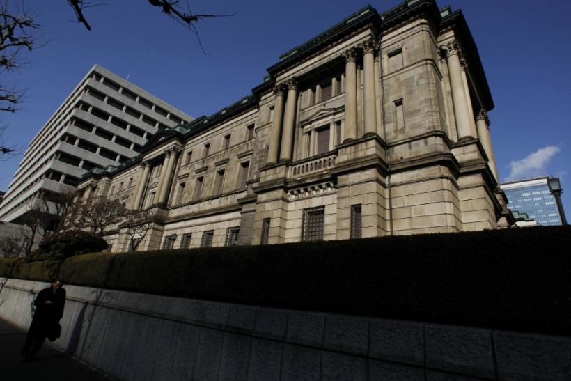 A pedestrian walks past the Bank of Japan (BOJ) headquarters in Tokyo February 15, 2011
