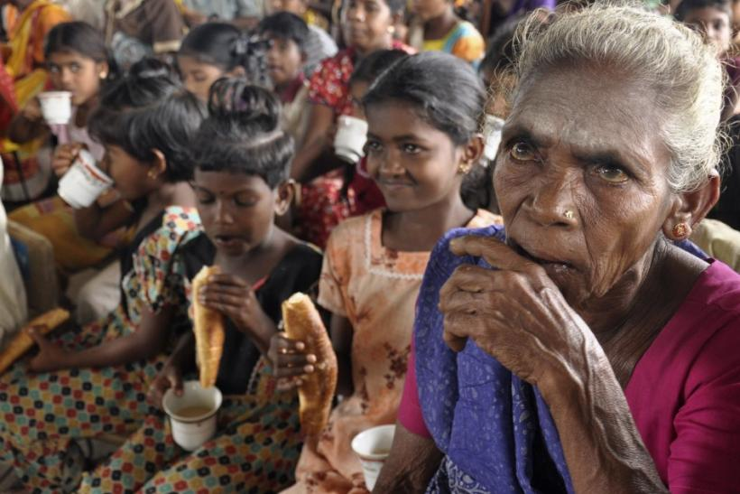 People displaced by flooding eat bread and drink tea in a temporary camp in Batticaloa district