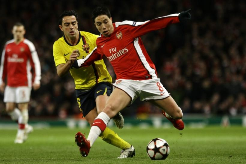 Arsenal's Nasri is challenged by Barcelona's Xavi during their Champions League quarter-final soccer match in London.