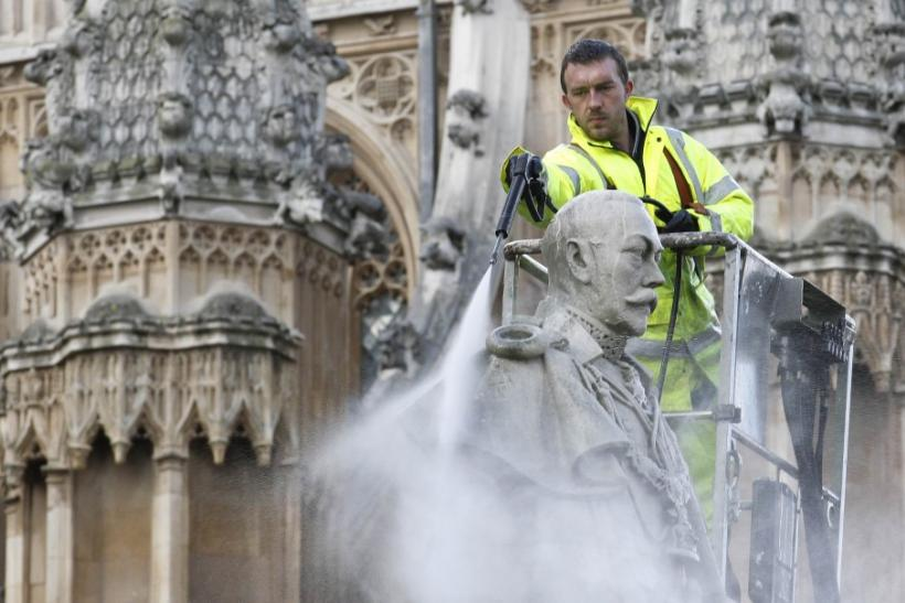 A worker uses a power washer to clean a statue of Britain's King George V outside Westminster Abbey in London