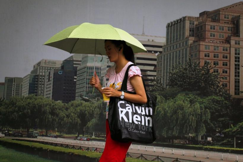 Woman holds an umbrella as she walks past a billboard carrying a bag displaying the name of U.S. fashion label Calvin Klein in central Beijing.