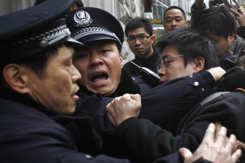 A man is arrested by police after internet social networks called to join a 'Jasmine Revolution' protest in front of the Peace Cinema in downtown Shanghai