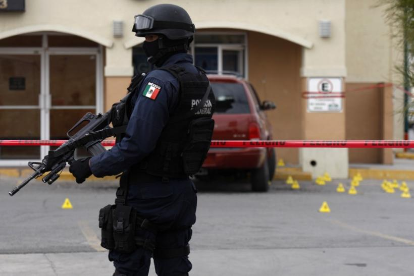 A police officer stands guard at a crime scene where two men were shot dead earlier in Ciudad Juarez