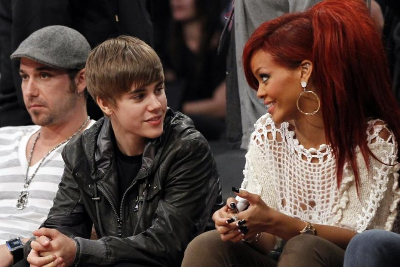 Justin Bieber talks with Rihanna as they sit courtside during the NBA All-Star basketball game in Los Angeles