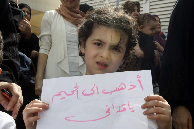 A girl holds a sign during a protest in solidarity with the anti-government protests in Libya, in front of the Libyan consulate in Dubai