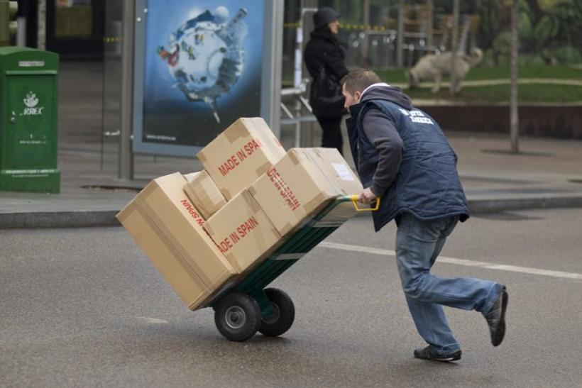 A worker pushes a trolley of boxes in central Madrid