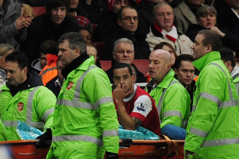 Arsenal's Theo Walcott watches his team play as he is carried off the pitch in a stretcher during their English Premier League soccer match against Stoke City at the Emirates Stadium in London.