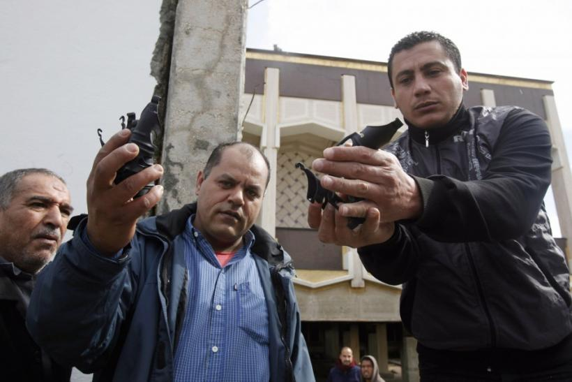Anti-government demonstrators show hand grenades, which were used by troops loyal to Libyan leader Muammar Gaddafi while fighting with demonstrators, in Benghazi city