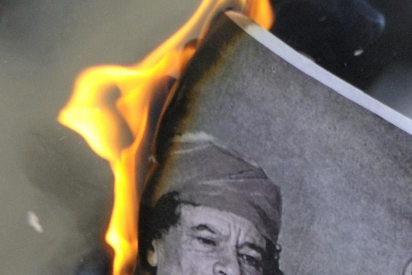 A man burns a picture of Libyan leader Muammar Gaddafi during a demonstration near the Libyan consulate in Paris