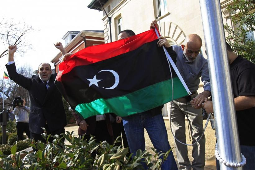 Demonstrators cheer as they raise a Kingdom of Libya flag at the residence of the Libyan ambassador in Washington