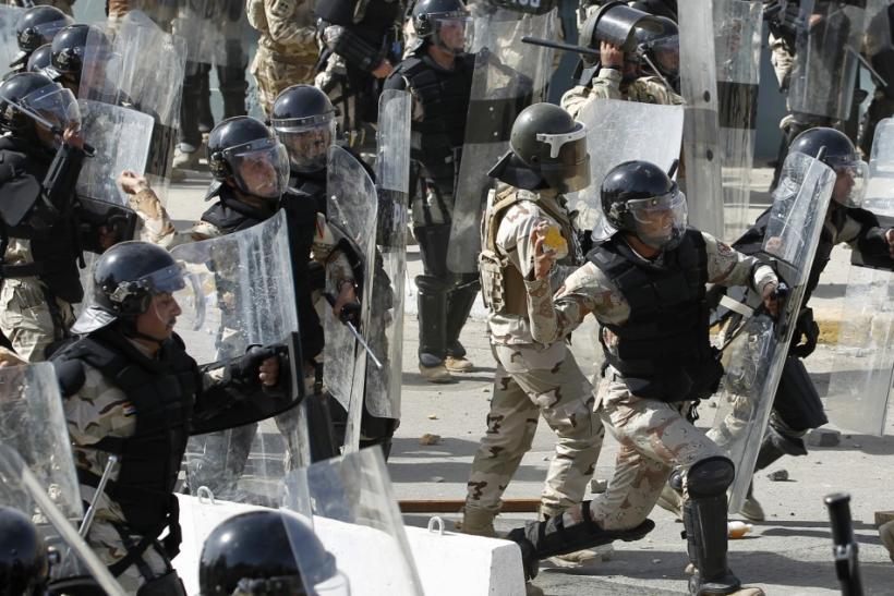 Riot police shield themselves from rocks thrown by protesters during a demonstration in central Baghdad