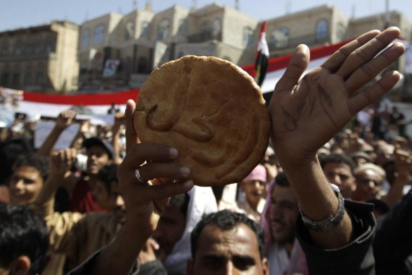 "A protester holds a piece of bread with the word ""Leave!"" on it during an anti-government rally outside Sanaa University"
