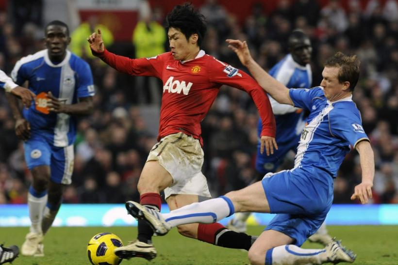 Wigan Athletic's Steven Caldwell (R) challenges Manchester United's Park Ji-sung during their English Premier League soccer match in Manchester.