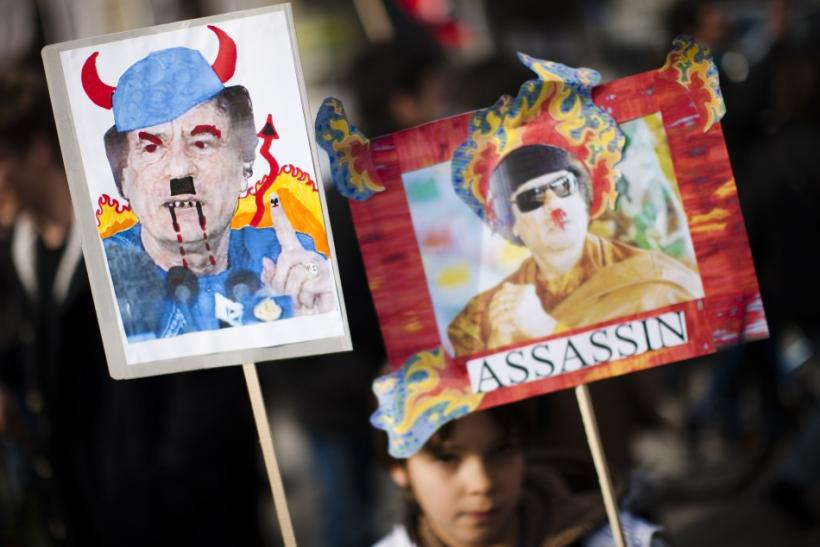 A young boy holds satirical posters of Libya's leader Gaddafi during a demonstration in solidarity with the anti-government protests in Libya, in Geneva