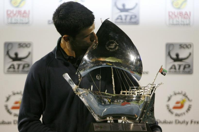 Novak Djokovic of Serbia poses with the trophy after winning his final match against Roger Federer of Switzerland at the ATP Dubai Tennis Championships.