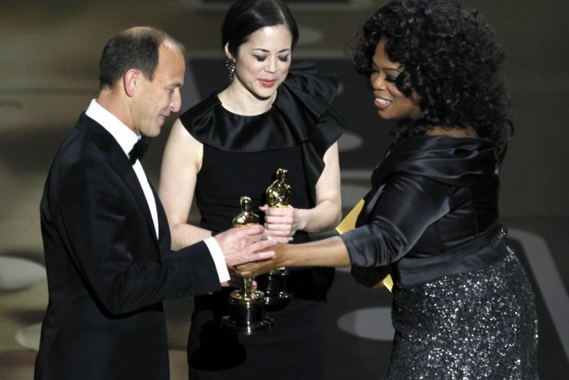 "Charles Ferguson and Audrey Marrs accept the Oscar for best documentary feature for ""Inside Job,"" from presenter Winfrey during the 83rd Academy Awards in Hollywood, California."
