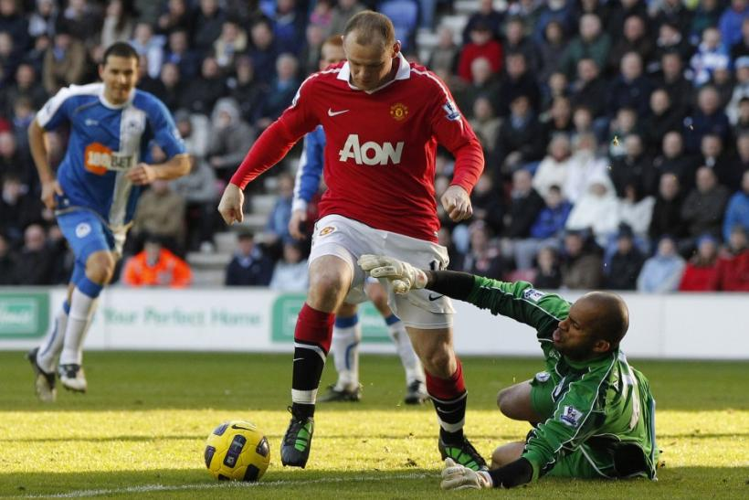 Wigan Athletic's al Habsi challenges Manchester United's Rooney during their English Premier League soccer match at the DW Stadium in Wigan.