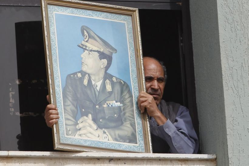 A man holds a picture of Libya's leader Muammar Gaddafi from the window of a bank in Sabratha