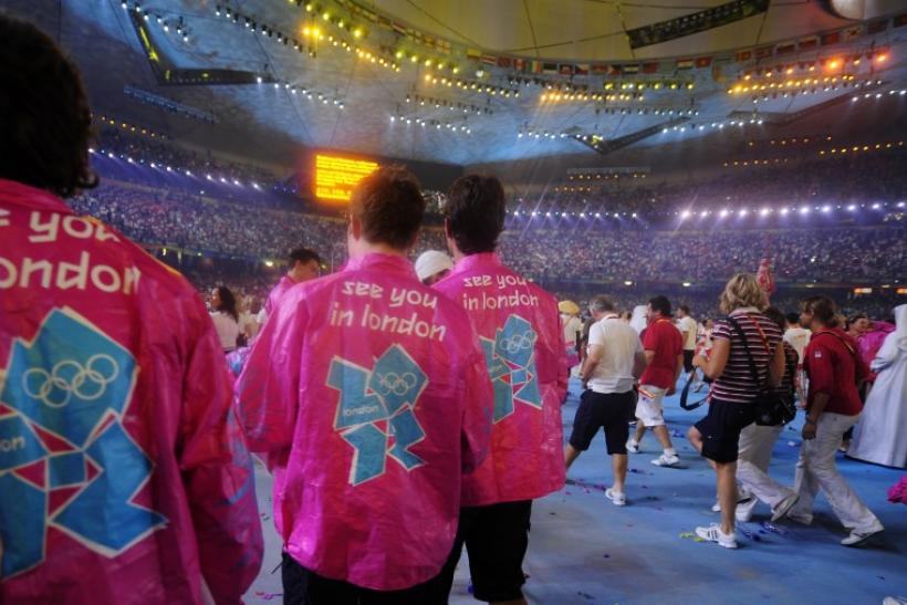 Participants wear shirts with the logo of the London 2012 Olympics during the closing ceremony of the Beijing 2008 Olympic Games at the National Stadium