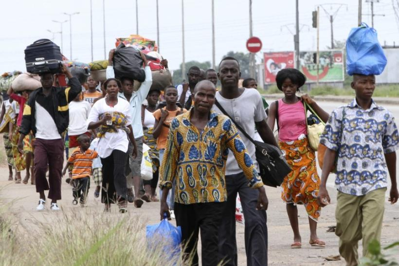 Residents flee with their belongings after clashes between forces loyal to incumbent president Laurent Gbagbo and his rival Alassane Ouattara in Abobo