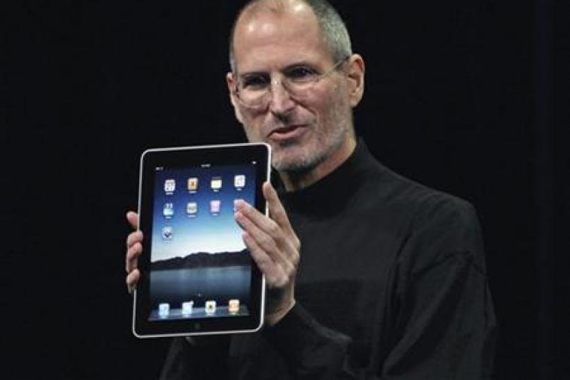 Apple CEO Steve Jobs holds tan iPad during the launch of Apple's new tablet computing device in San Francisco