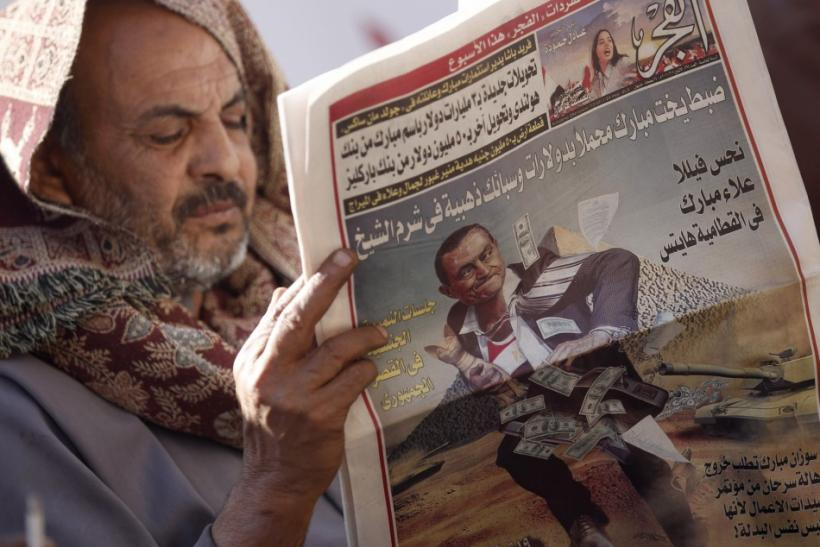 A man reads a local newspaper at Tahrir Square in Cairo