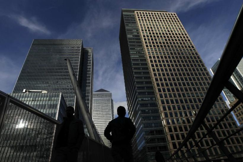 Silhouetted workers walk in front of office towers in the Canary Wharf financial district in London