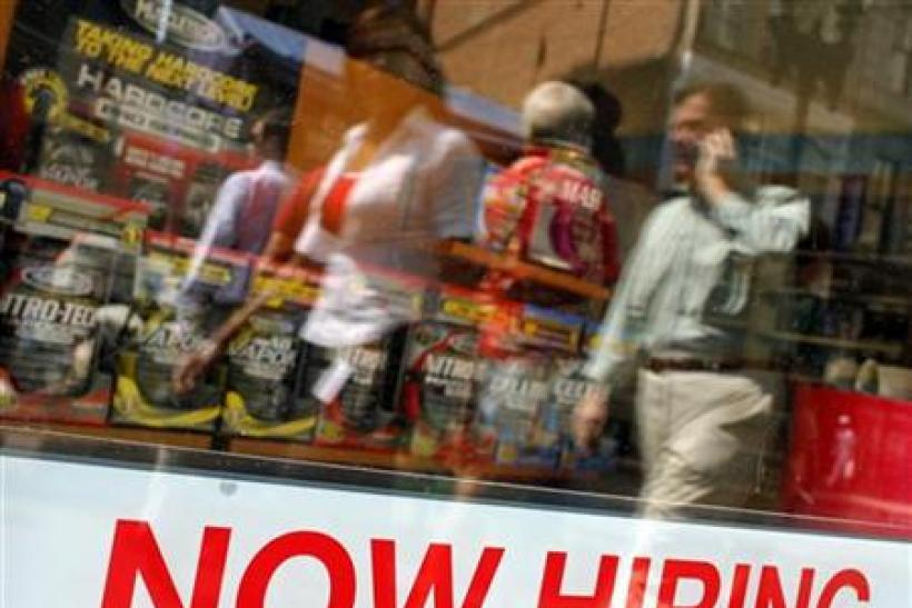"Pedestrians walk past a ""Now Hiring"" sign in the window of a GNC shop in Boston, Massachusetts"