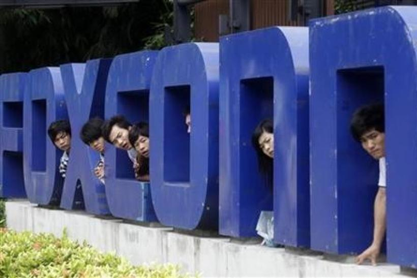 Workers look on from a Foxconn logo near the gate of a Foxconn factory in the township of Longhua, Guangdong province May 29, 2010.