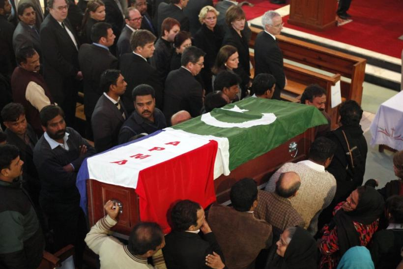 Men carry the casket, wrapped in national and party flags, of Pakistan's Minister for Minorities Shahbaz Bhatt during a funeral ceremony in Islamabad