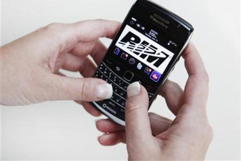 A person poses while using a Blackberry Bold 2 smartphone made by Research in Motion