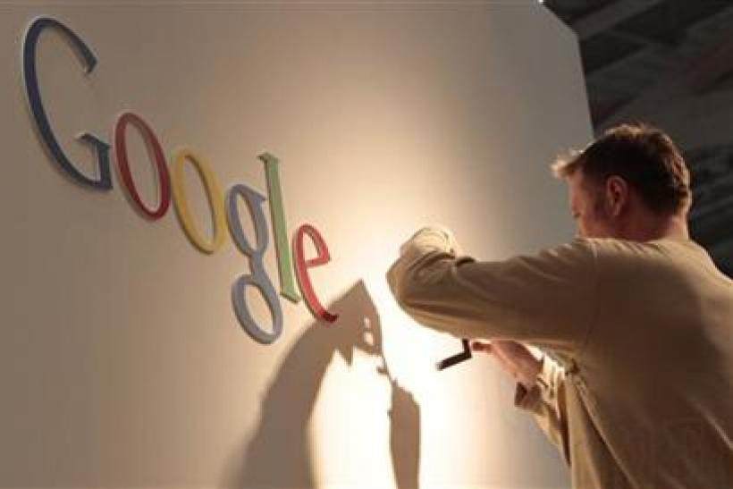 Man works on Google logo at exhibition stand at CeBIT computer fair in Hanover