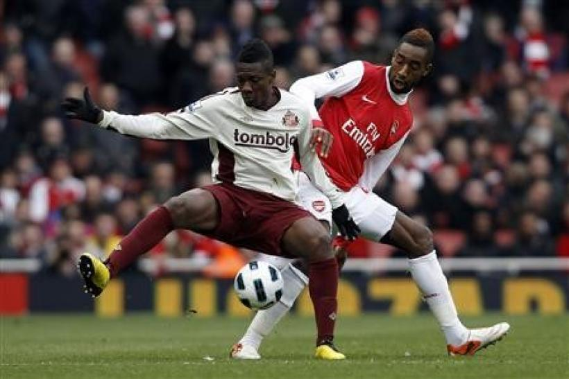 Arsenal's Johan Djourou (R) challenges Sunderland's Asamoah Gyan during their English Premier League soccer match at Emirates Stadium in London March 5, 2011.