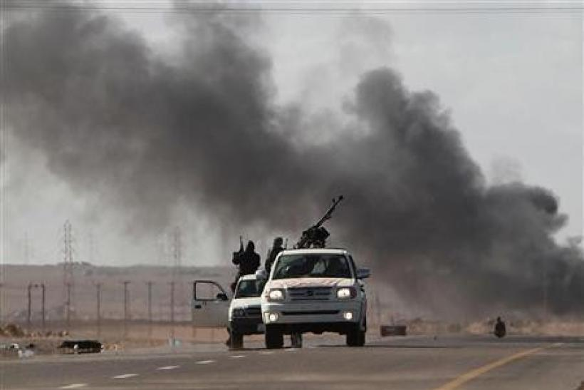 Anti-Gaddafi rebels retreat after a mortar attack by pro-Gaddafi forces
