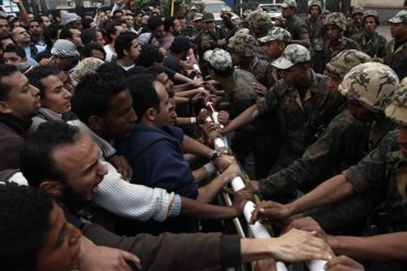 Egyptian protesters stand before army soldiers in front of the state security headquarters in downtown Cairo