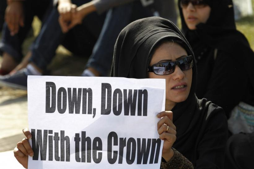 A female anti-government protester holds a banner during a protest at the Bahrain Financial Habour in Manama