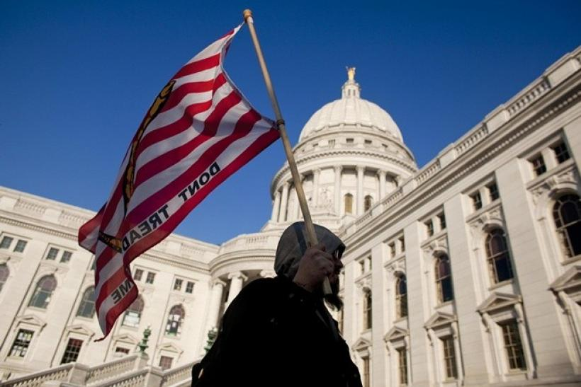 "A man marches with a ""don't tread on me"" flag outside the State Capitol building in Madison, Wisconsin on February 28, 2011."