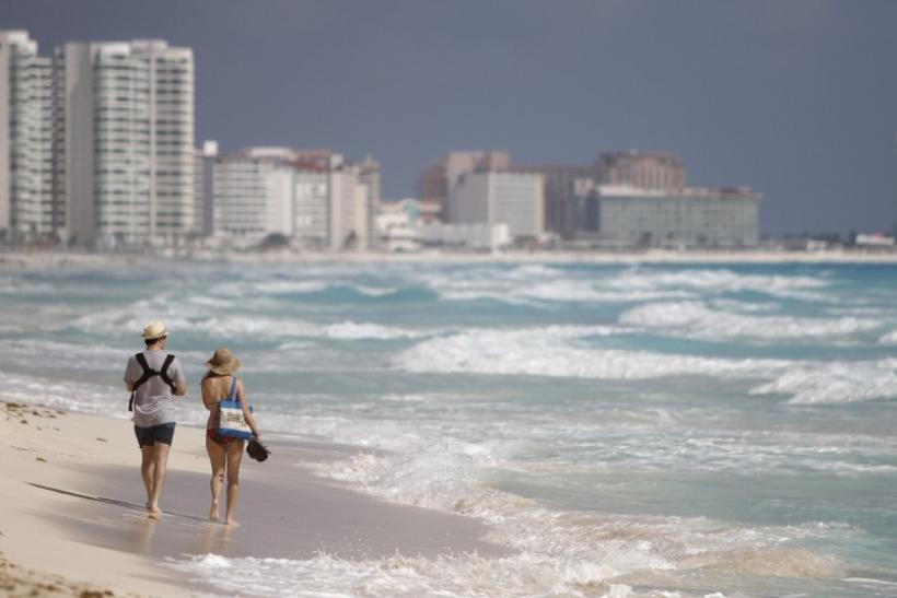 A couple walks along Marlin beach in Cancun February 1, 2011.