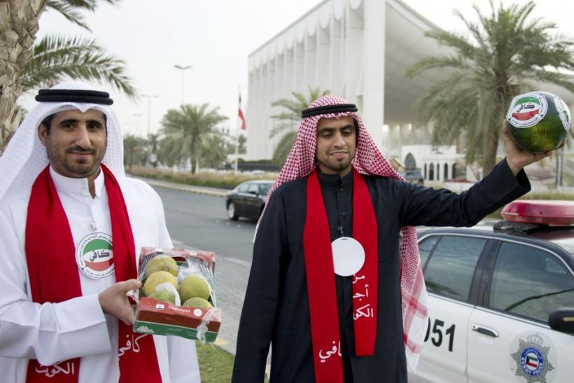 "Two men from the Kuwaiti youth movement ""Kaafi"" hold watermelons as a protest in front of the Parliament building in Kuwait City"