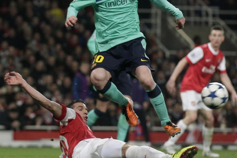 Arsenal's van Persie fights for the ball against Barcelona's Messi during their Champions League soccer match in London.