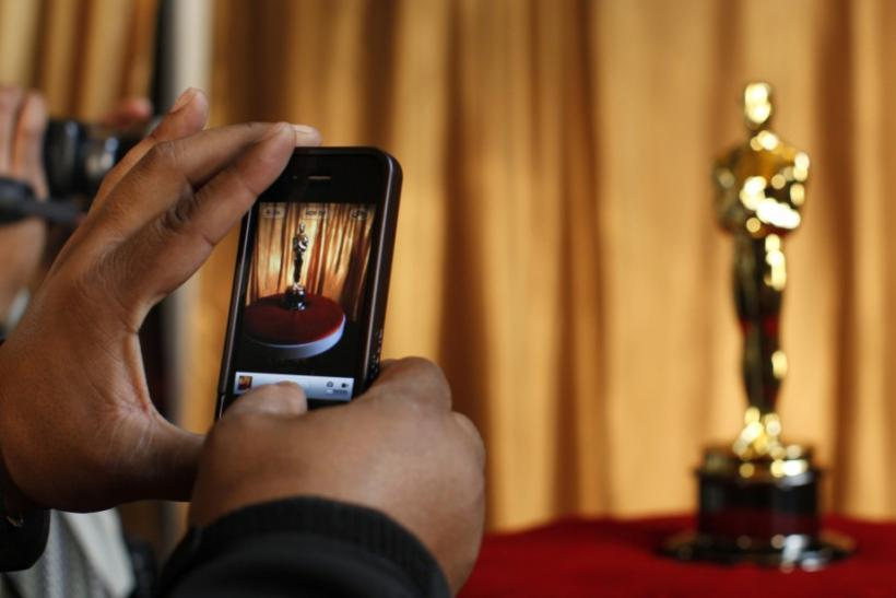 "A man photographs an Oscar statuette using his phone at the ""Meet the Oscars"" exhibit at Grand Central Station in New York February 23, 2011"