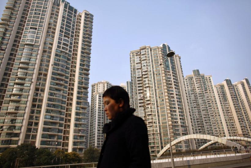 A woman walks in front of a residential site in Shanghai March 2, 2011.