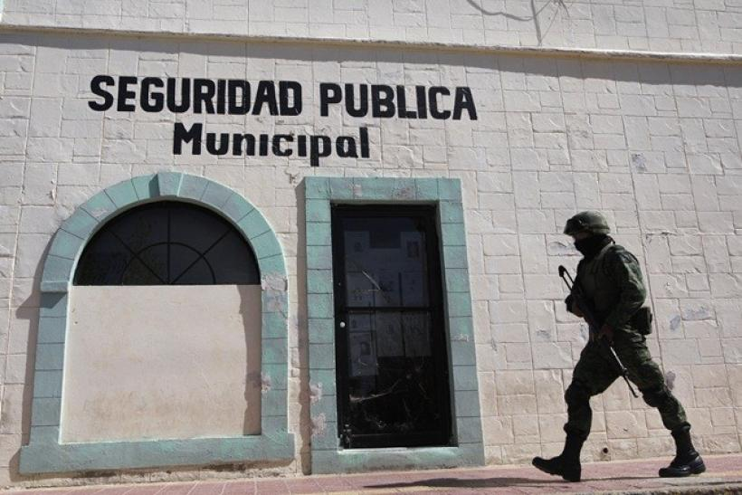 A soldier walks past the police headquarters where Marisol Valles Garcia used to work as the police chief in Praxedis G. Guerrero March 7, 2011.